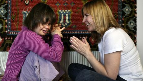 Barnet och den vuxna sitter mittemot varandra och klappar händerna och skrattar.