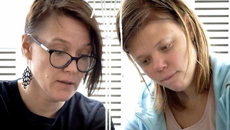 Två kvinnor vid samma arbetsuppgift.