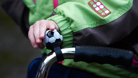 Lapsen käsi polkupyörän pirikellon päällä, kello näyttää pieneltä jalkapallolta.