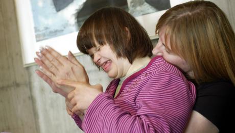 kehitysvammainen henkilö työntekijän sylissä, taputtavat käsiään yhdessä ja nauravat