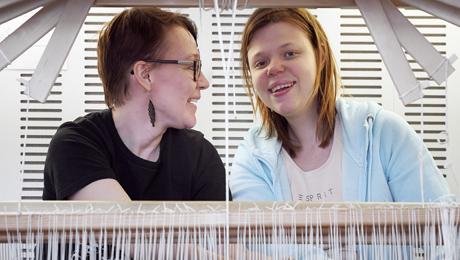 kaksi naista kangaspuiden äärellä iloisina