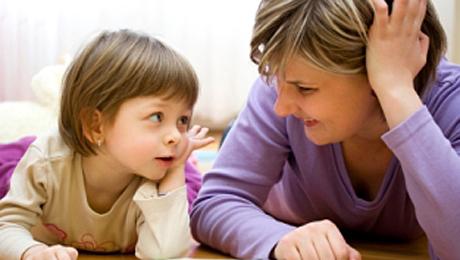 Lapsi ja aikuinen katsovat toisiaan silmiin.