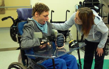 nainen kumartuneena kohti pyörätuolissa istuvaa miestä ja pitää kättä tämän harteilla