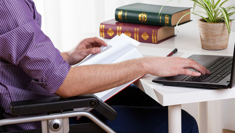 En människa i rullstol vid ett bord med en bärbar dator. På bordet finns papper och lagböcker.