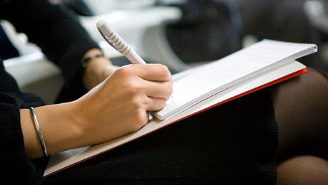 Käsi ja kynä, valmiina kirjoittamaan edessä olevalle paperille.