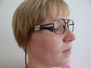En kvinna som har en blinkningskontakt fäst vid glasögonen.