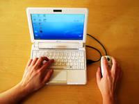 Minilaptop och händer på tangentbordet.